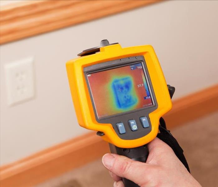 Thermal imaging device directed at a wall showing moisture content