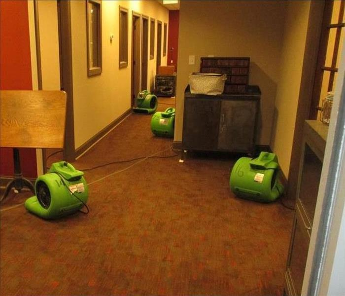 Four air movers drying the carpet in this hallway